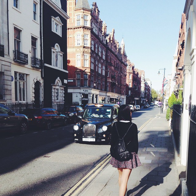 Ling Cai wandering down Bond Street in London in a Chanel backpack.